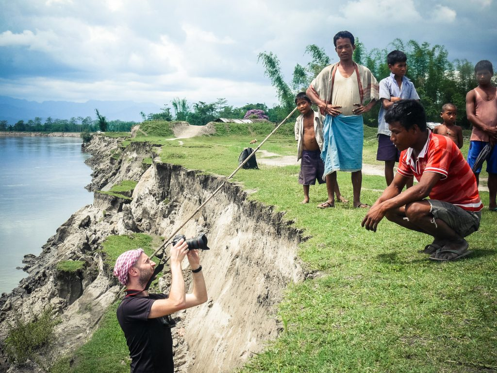 Backstage of the Reportage on the Brahmaputra (Assam, India). French photographer Franck Vogel shooting a portrait of Debo Pamegam (28y), who had to move his house already 3 times (July '12, Aug '12 and March '13) with his wife Mampuli (25y) and their 3 children (Musukundo, Sunukundo and Junmoni). Photo taken in May '13. The Subansiri shore is was constantly eroding. At Kanuapra, a Mising village, near Gogamukh on the Subansiri river, erosion is a huge problem: 55 houses have already been moved several times. The original village land has disappeared and the owner of the land, where they moved, want them to find another place. Biren Pegu, the Mising leader tries to negociate with politicians (MLA) to get a new land for free. Since the dam construction on Subansiri, 33 villages have been destroyed by erosion.