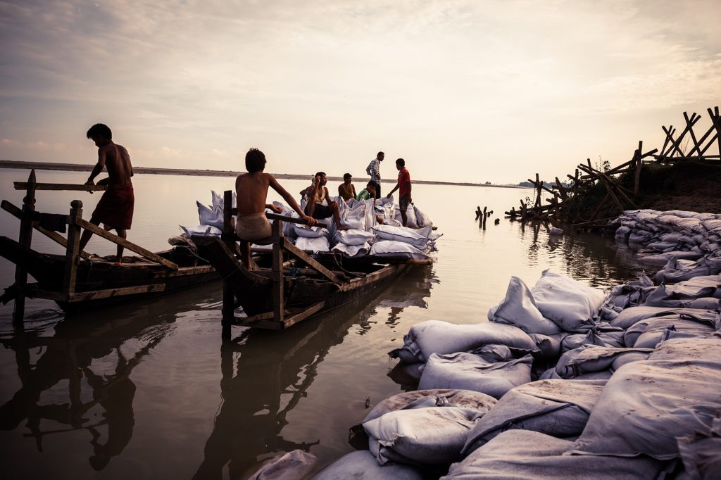 To prevent erosion, the Brahmaputra Board hires workers to fill sand bags on small sand islands that will be used on Majuli. In the background bags are being filled on the other shore. 