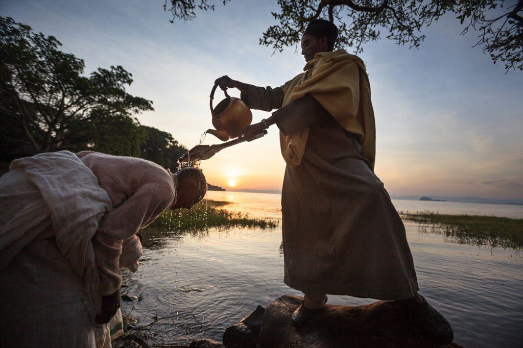 Ethiopia – After the Divine Liturgy, lake Tana'€™s water is blessed by a priest from the nearby Ura Kidane Mihret monastery and sprinkled on the crowd. Some pilgrims immerse themselves, symbolically renewing their baptismal vows.     Timkat is Ethiopian most important orthodox celebration. It symbolizes both Jesus baptism in the Jordan river and Epiphany. It takes place on January 19 (the 20th for leap years) all over the country. On Timkat's eve, a colorful and joyful procession starts from Orakidanu Bret monastery on Zege peninsula, near Bahir Dar. A priest holds the Tabot, which represents the manifestation of Jesus as the Messiah when he came to the Jordan for baptism. When the crowd reaches lake Tana - source of the Blue Nile - they pray and sing all night long. At 4am, the lake's water is blessed by priests and sprinkled on the crowd. Some pilgrims immerse themselves, symbolically renewing their baptismal vows.  Lors de la fête religieuse de Timqet (Pâques orthodoxe) sur la presqu'île de Zege au monastère Ura Kidane Mihret en Ethiopie. Après avoir veillé toute le nuit au bord du lac Tana à la belle étoile - il fait un froid de canard. Au petit matin, les croyants vont se faire asperger d'eau en rentrant dans l'eau du lac sacré...source du Nil Bleu et source de vie. Le Timqet est la célébration éthiopienne orthodoxe à la fois du baptême de Jésus dans le Jourdain et de l'Épiphanie. Elle a lieu le 19 janvier (le 20 pour les années bissextiles). La fête est connue pour sa reconstitution rituelle du baptême (similaire aux reconstitutions de nombreux pèlerins chrétiens en Terre Sainte lorsqu'ils se rendent au Jourdain). Timqet est une des cérémonies durant laquelle les tabots (répliques de l'Arche de l'Alliance) sont retirés des églises pour être vus par la foule, des tissus sont toutefois enroulés autour. Pendant la procession, qui a lieu la veille, les prêtres, vêtus de costumes colorés, portent les tabots sur leur tête pour les